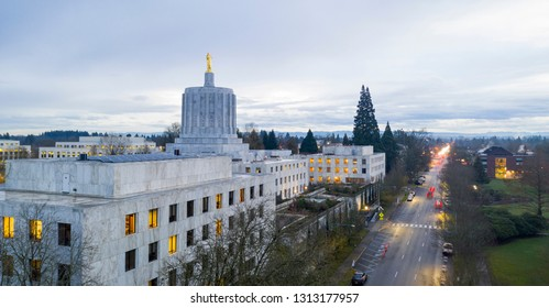 The state capital building adorned with the Oregon Pioneer with downtown Salem in the background
