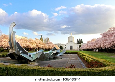 State Capitol building with gold Pioneer sculpture / statue. View from the park with abstract fountain and cherry blossom tree alley. Salem, Oregon on April 2, 2018.