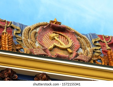 """State emblem of the former Ukrainian Soviet Socialist Republic with gold sickle and hammer and  inscriptions: """"Ukrainian RSR"""",""""Workers of all countries, unite!"""", """"Proletarian All-Ukrainian, come on!"""""""