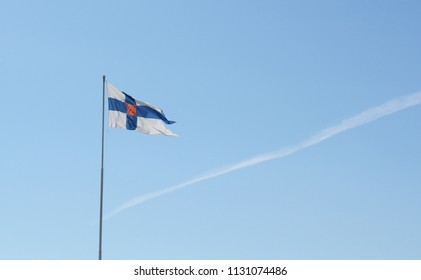 State flag of Finland flies from a flagpole against a light blue sky with a single contrail