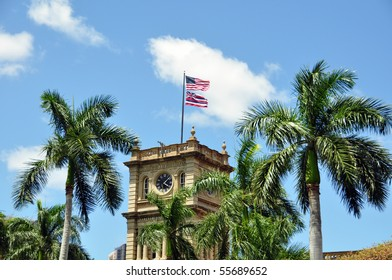 State flag of the Hawaiian Islands  in front of Palm tress.