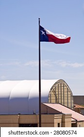 The state flag of Texas flying in a breeze, photographed above some buildings in bright sunlight, against a deep blue sky.