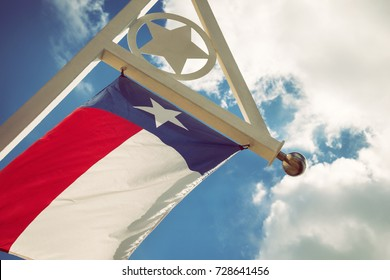 State flag of Texas waving in the wind on a sunny day. Blue sky with white clouds background.