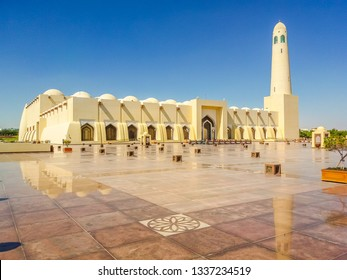 State Grand Mosque with a minaret reflecting on marble pavement outdoors. Doha mosque in Downtown, Qatar, Middle East, Arabian Peninsula. Morning daylight shot. Sunny day with blue sky.