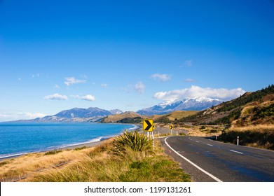 State Highway 1, iconic coastal route near Kaikoura, New Zealand, considered to be one of the top coastal drives in the world. Snow capped mountains meet sea, sky and road.