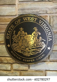 State seal of West Virginia, showing state motto in Latin, along with illustration of miners and state founding date.