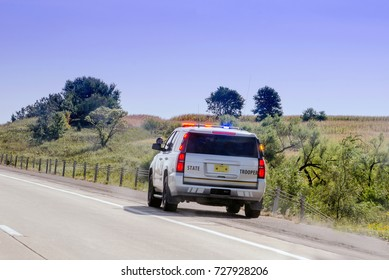 state trooper on road side with lights flashing