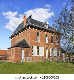 Stately ancient parsonage against cloudy blue sky, Ravels, Flanders, Belgium