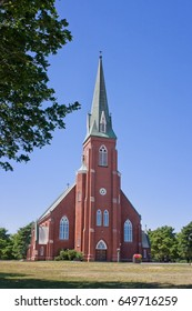 Stately brick church with steeple against a rich blue summer sky
