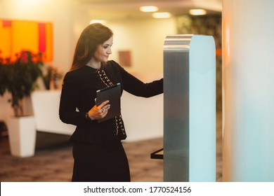A stately charming caucasian woman entrepreneur in a black formal suit, with a digital tablet in one hand, is interacting with an electronic terminal while standing indoors of a modern business office