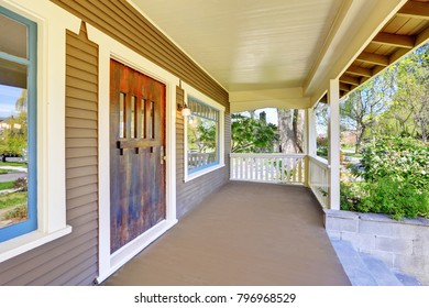 Stately completely renovated Craftsman home exterior: covered empty entrance porch accented with white trim. This historic home was designed and constructed by Henry Schneider.