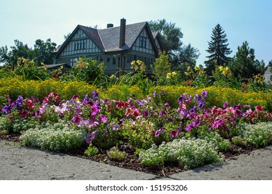 A stately home with large flower garden.