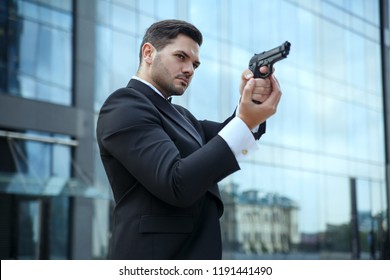 A stately white man with a gun in his hands.