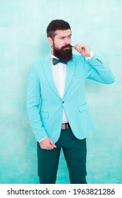 Statement with his stunning crisp suit jacket. Stylist fashion expert. Suit style. Fashion trends for groom. Groom bearded hipster man wear light blue tuxedo and bow tie. Wedding day. Stylish groom