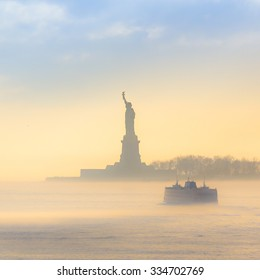 Staten Island Ferry cruises past the Statue of Liberty on a misty sunset. Manhattan, New York City, United States of America. Square composition.