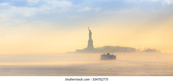 Staten Island Ferry cruises past the Statue of Liberty on a misty sunset. Manhattan, New York City, United States of America. Panoramic composition. Copy space.