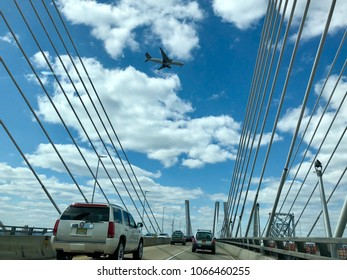 STATEN ISLAND, NY - APRIL 8, 2018: A plane flies over the newly conrtucted Goethals Bridge connecting Elizabeth, New Jersey, to Staten Island, New York, in the United States.