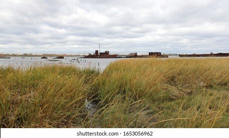 Staten Island, NY/USA - October 17, 2019: Marshland on the shore of the Arthur Kill strait, rusting vessels in the ships graveyard in the background