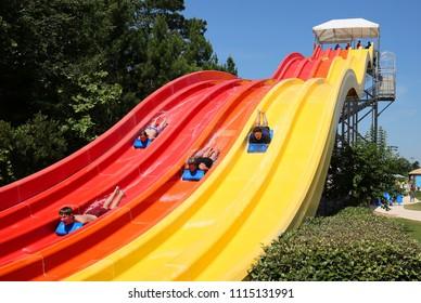 STATESBORO, GEORGIA, USA - JUNE:  Friends go down the big slide at Splash in the Boro a family waterpark and aquatic center as seen on June 6, 2018.