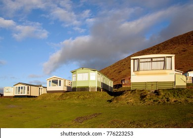 Static caravan holiday homes at Llangennith on the Gower Peninsular in winter which is out of season, the caravans are closed up until spring and the park is empty of people.