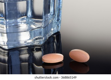 Statin tablets with a glass of water. Health/Medical concept
