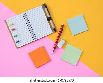 Stationary Background. Flat Lay Photo of Stationary with Notebook and post it and stationary on pink and yellow background