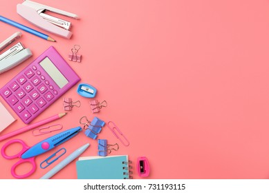 Stationary concept, Flat Lay top view Photo of Scissors, pencils, paper clips,calculator,sticky note,stapler and notepad in pink and blue tone on pink background with copy space.
