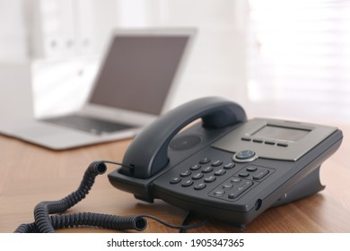 Stationary phone on wooden table indoors, space for text. Hotline service - Shutterstock ID 1905347365