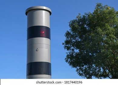 Stationary speed limit enforcement, traffic monitoring with light radar and camera, speeding may result in a monetary fine or driving license revocation, blue sky, copy space
