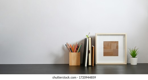 Stationary in wooden pencil holder putting on wooden working desk that surrounded by books, notebook, empty picture frame and potted plant over sitting room white wall as background.