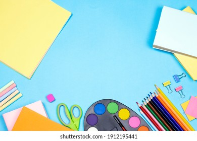 Stationery accessory on blue background. School supplies, pencils, paints, scissors, and colored books, on blue background with copy space. Education and freelancer work concept.