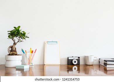 Stationery books, papers, coffee mug, vintage camera and bonsai tree on office desk