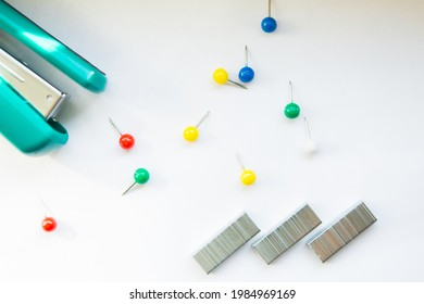 Stationery buttons, staples and stapler on white background