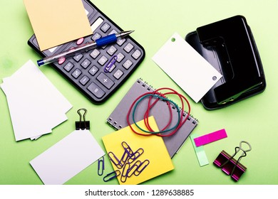 Stationery and calculator. Notebook, bookmarks, elastics and clips on green background. Office supplies and business concept. Business cards with copy space and binders near sticky notes and puncher.