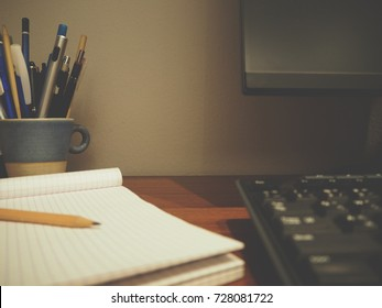 Stationery, computer and keyboard are on the table as  warm dark tone