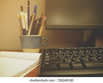 Stationery, computer, keyboard are on the table as warm dark tone
