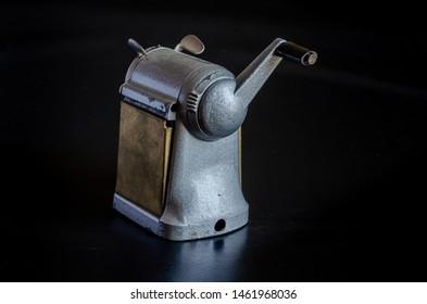 Stationery items of the last century. Mechanical manual sharpener. Macro. Dark background.