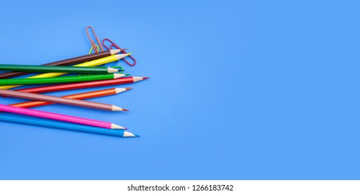 Stationery office supplies concepts wide banner template design, Colored crayon pencils and clips on blue background with copy space. Top view, Closeup.
