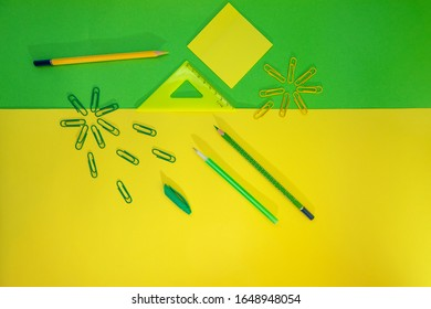 Stationery for school and office on a yellow-green background, top view, there is space for text. Back to school. The concept of creative school.