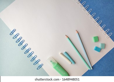 Stationery for school and office in pastel colors on a blue and white background, top view, there is space for text. Back to school. Creative school concept.