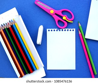 Stationery for school on a blue background. Notepad, a set of colored pencils, scissors, an eraser. Concept back to school, preparation for school