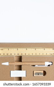 Stationery set of eco-friendly materials. Wooden pencil, sharpener, cardboard pen and eraser on the white background with copy space
