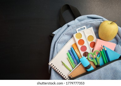 Stationery set with knapsack on black background. School supplies top view for advertising and promotional items. Back to school concept