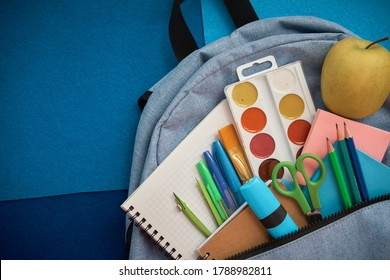 Stationery set with knapsack on blue background. School supplies top view for advertising and promotional items. Back to school concept
