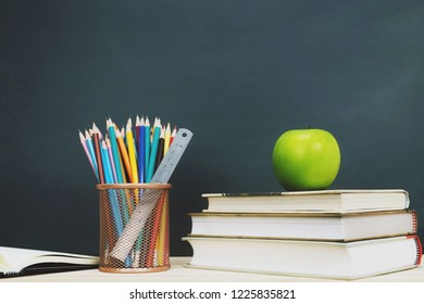 Stationery Supplies and accessories Chalk,Crayon, Pencil,Ruler,apple green, book, put on the desk wooden stationery blackboard background. Education back to school concept