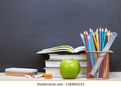 Stationery Supplies and accessories, Color Chalk,eraser,Crayon, Pencil,Ruler ,sharpener,pen, apple green, book, put on the desk Stationery Blackboard Background. Education back to school concept