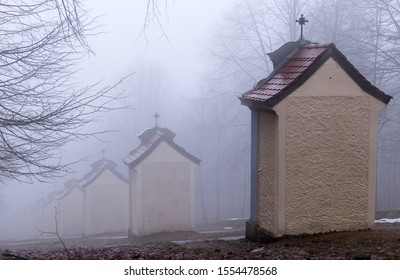 Stations of the Cross on a hill in winter fog. Clouds before sunset hiding buildings of the Stations of the Cross.