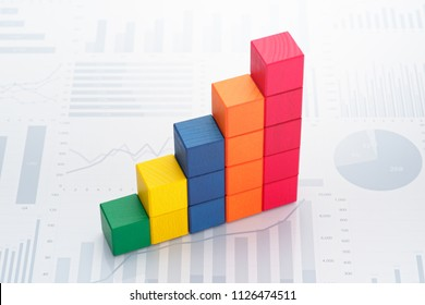 Statistical data analysis. Business data processing. Colorful toy block steps on many charts and graphs background.