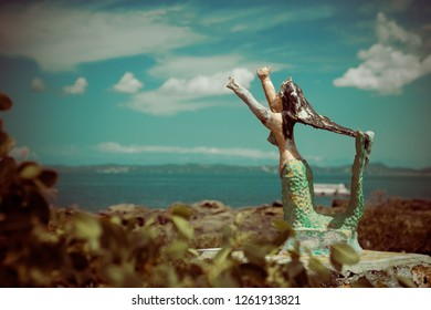Statue of an abandoned mermaid on the beach
