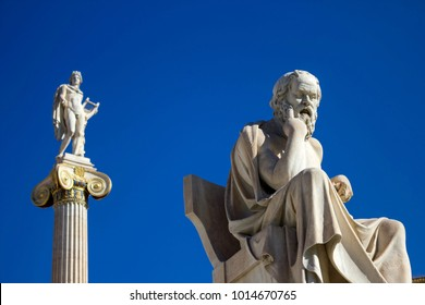 Statue of the ancient Greek philosopher Socrates in front of the Academy of Athens in Athens, Greece, with the statue of the ancient Greek God Apollo in the background.